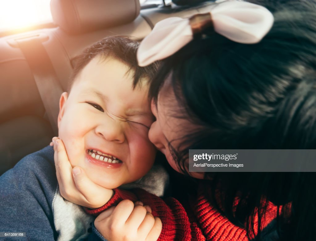 Sister Kissing Her Brother in Car : Stock Photo