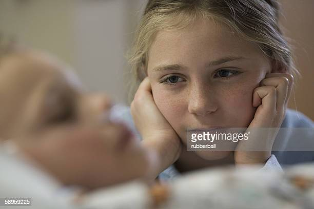 Sister looking at her brother lying in a hospital bed