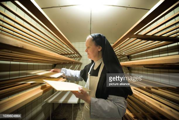 Sister Lucilla, prioress of the Carmelite monastery in Roedelmaier, places several sheets of sacramental bread on the shelf of a drying room in...