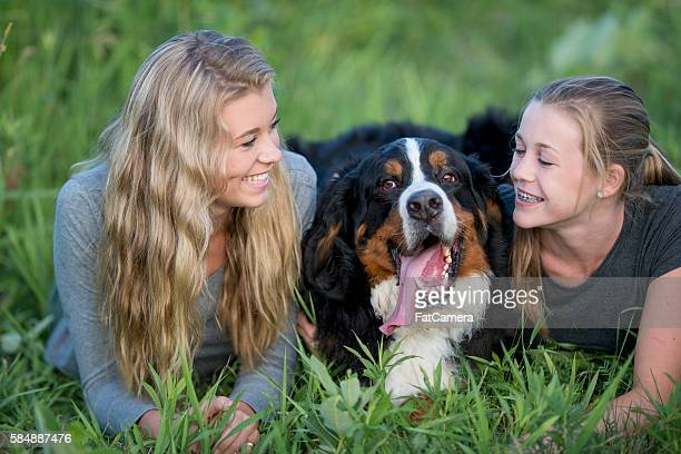 Sister Lying in the Grass with Their Pet