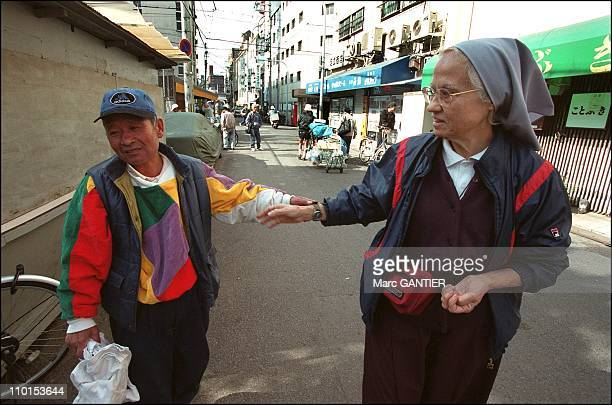 Sister Maria in Kamagasaki neighborhood with a homeless man in Osaka Japan on March 2002