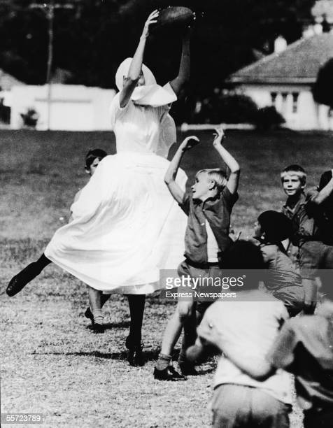 Sister Marie Louise makes use of her height advantage and catches the ball during a game of rugby against small boys mid 20th Century