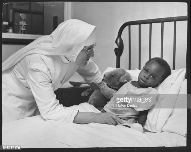 Sister Mary Catherine talks to a Biafra child who was a victim of the Nigerian Biafran War and is in Britain for medical care