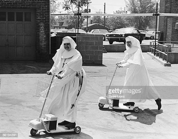 Sister Mary Thomas , an administrator at St Elizabeth's Hospital, convinces another nun of the convenience of an electric scooter, circa 1955.