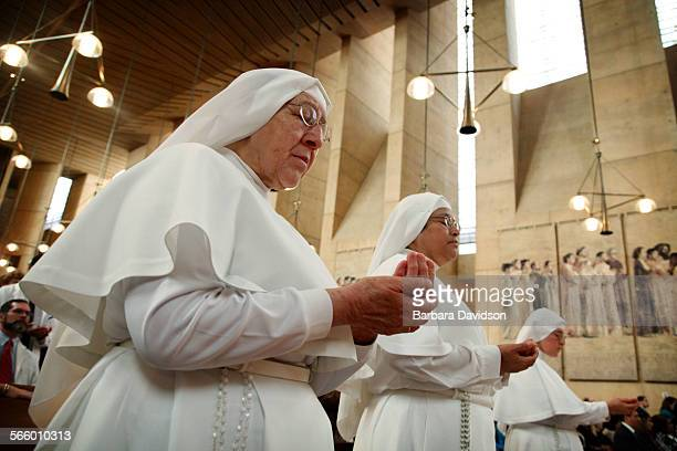 Sister Pilar, Sister Victorina, and Mother Angelica hold out their hands to be blessed during a White Mass at the Cathedral on Sunday Oct. 27. 2013...