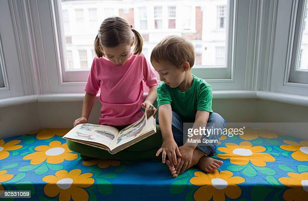 Sister reading to little brother