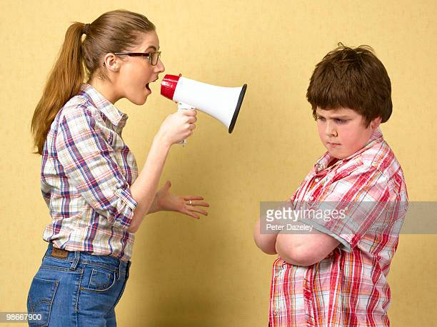 Sister shouting at brother with megaphone