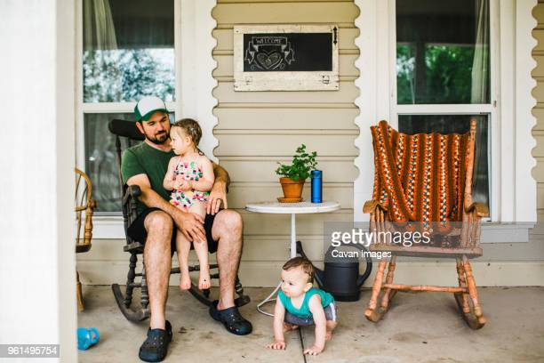sister sitting on father's laps while brother crouching at porch - rocking chair stock pictures, royalty-free photos & images