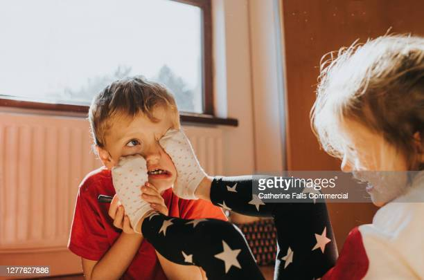 sister sticks her feet in her brothers face - offspring stock pictures, royalty-free photos & images