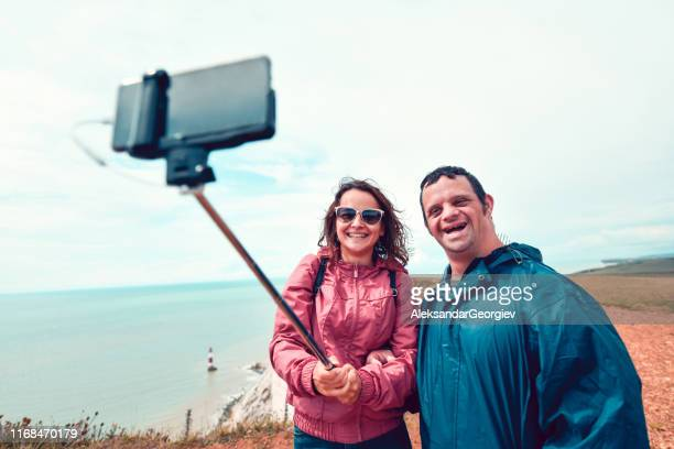 hermana tomando selfie con hermano discapacitado - discapacidad intelectual fotografías e imágenes de stock