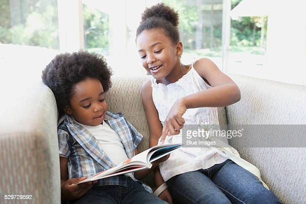 sister teaching her brother how to read - sister stock pictures, royalty-free photos & images