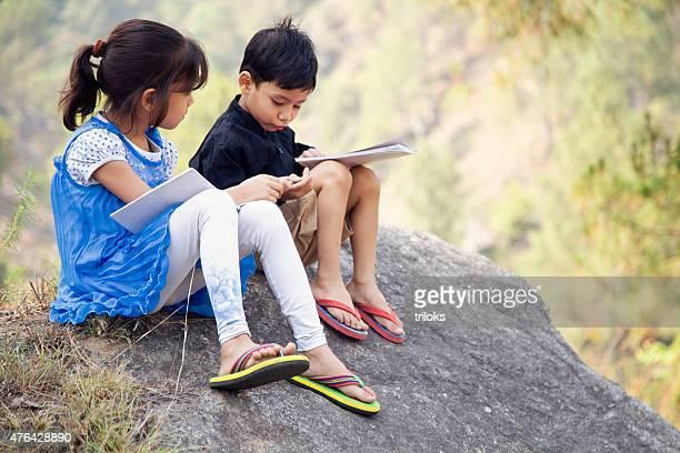 村の女の子と男の子勉強する屋外