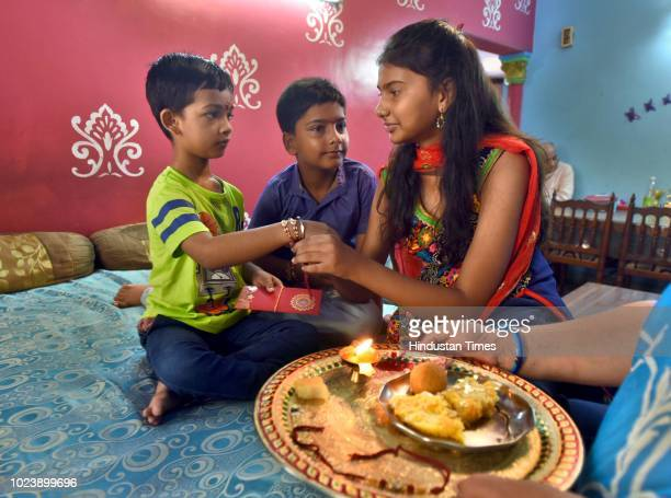 A sister ties rakhi on her brother's wrist on the occasion of Raksha Bandhan as her mother and grandmother look on at Mayur Vihar on August 26 2018...