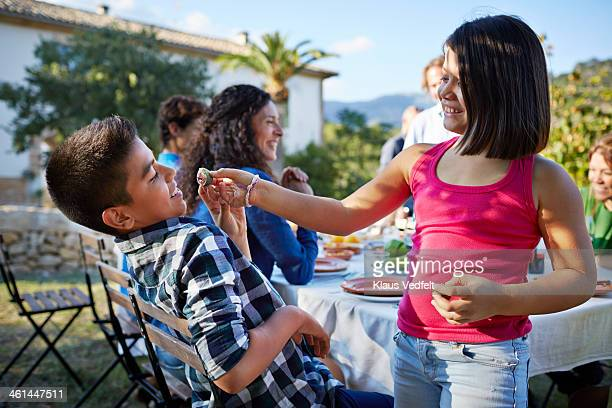 sister trying to feed brother with fresh fig - klaus vedfelt mallorca stock pictures, royalty-free photos & images