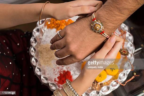 sister tying rakhi on her brother wrist - raksha bandhan stock photos and pictures