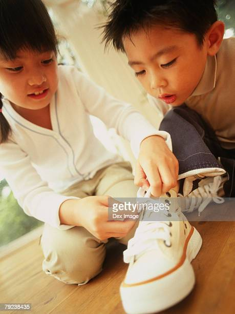 Sister tying shoelaces for brother