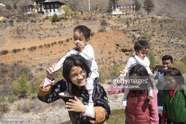 Sister Ugyen Choden and mother Bhumchu Zangmo carry twins Nima and Dawa Pelden as they walk towards Tachogang Lhakhang Monastery in Paro Valley in...
