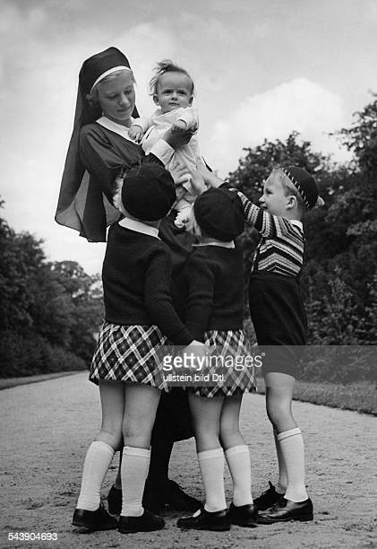 A sister wearing a baby on her arms encircled by children two girls wearing small tartan skirt and berets and a boy in a striped pullover ca 1935...
