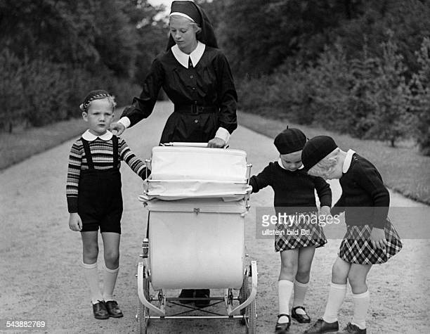 A sister with a pram encircled by children two girls wearing small tartan skirt and berets and a boy in a striped pullover and short trousers ca 1935...