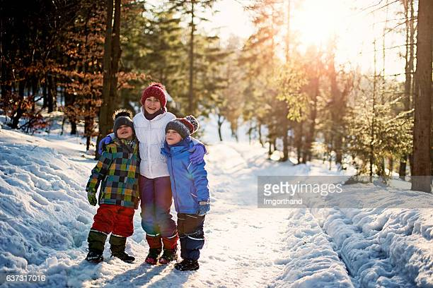 Sister with little brothers playing in winter forest