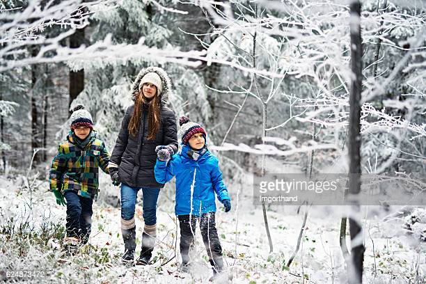 Sister with little brothers walking in frozen winter forest