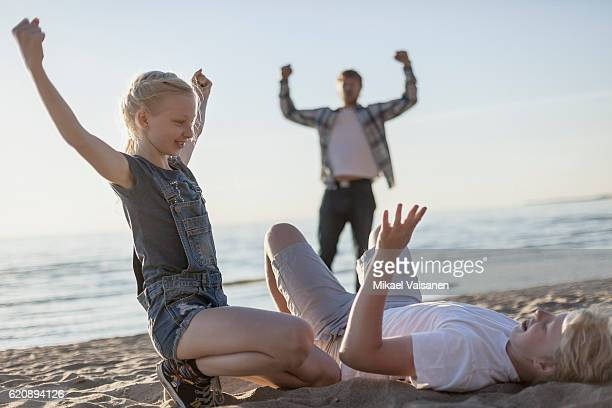 Sister wrestling with her brother on the beach