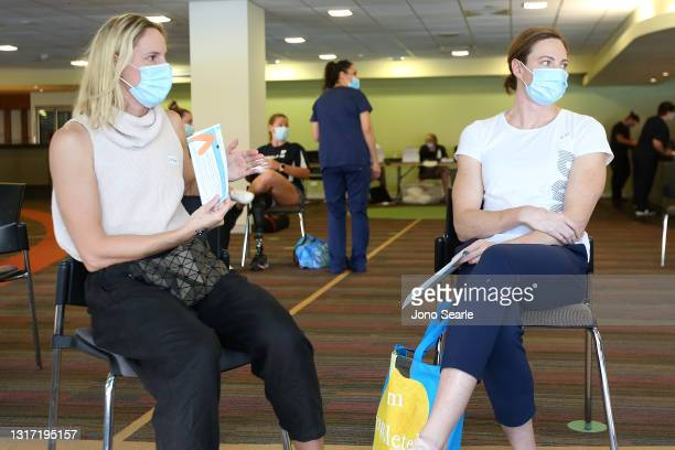 Sisters and Australian swimmers Bronte and Cate Campbell wait in a holding area after having their vaccination against Covid-19 during a media...
