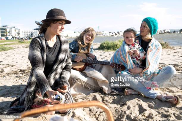 sisters and their children enjoying beach - aunt bildbanksfoton och bilder