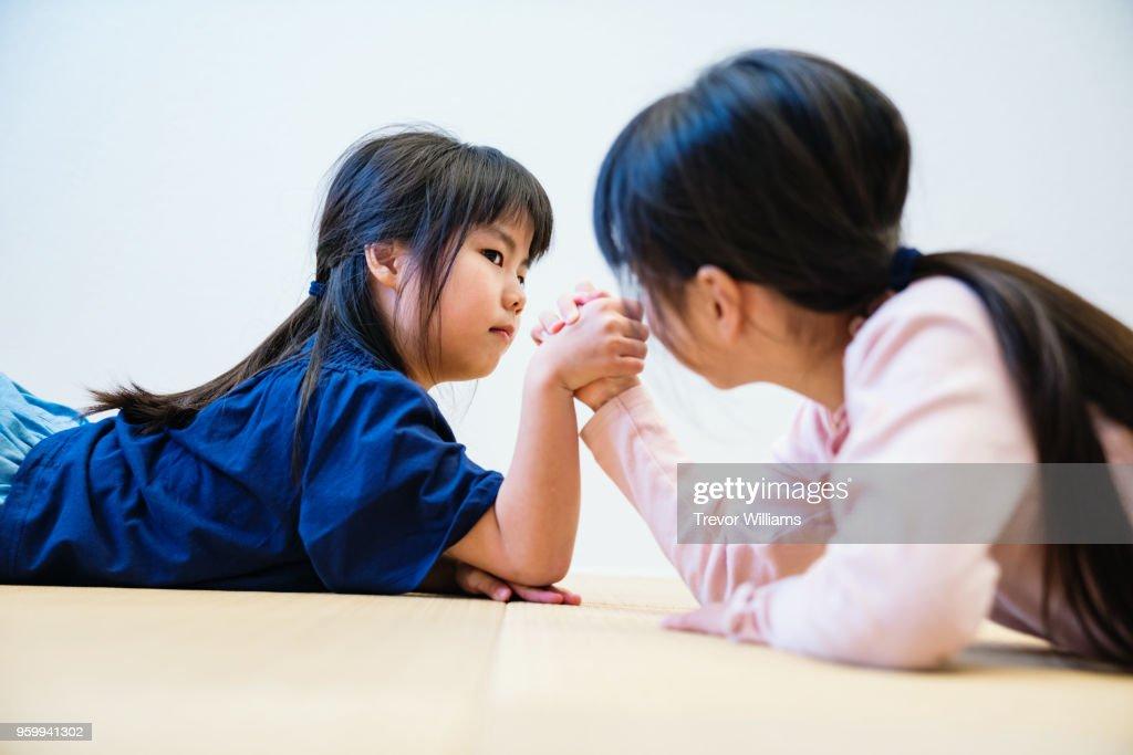 Sisters arm wrestling together : Stock-Foto