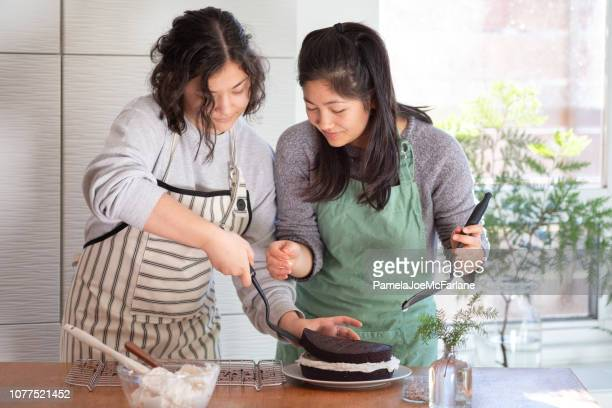 sisters assembling chocolate layer cake with vanilla icing in kitchen - hygge stock pictures, royalty-free photos & images