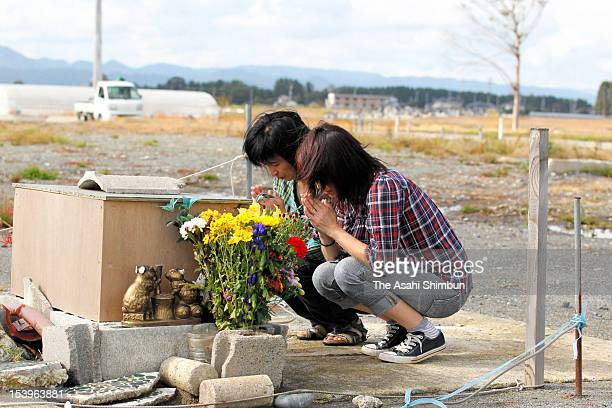 Sisters Atsuko Honma and Yasuko Sato offer flower bunches at their parents' home used to stand on October 11 2012 in Minamisoma Fukushima Japan Their...
