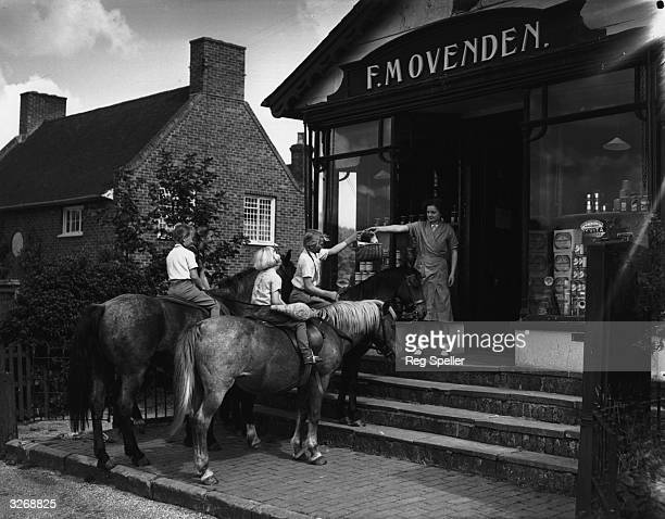 Sisters Barbara Judith and Susan Poile riding ponies to the village shop in Fordcombe near Tunbridge Wells in Kent 7th September 1943