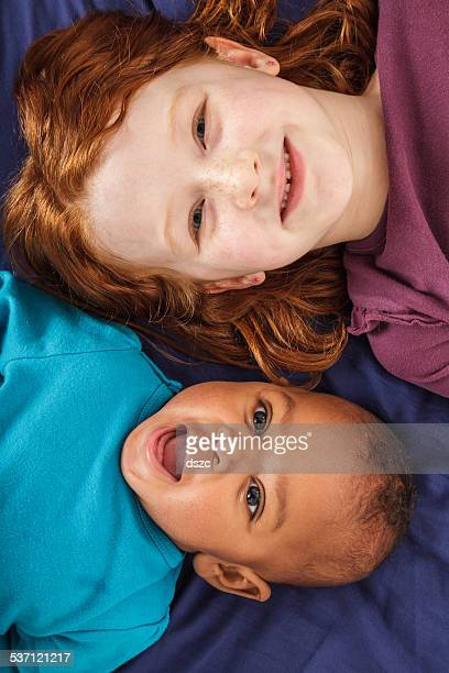 sisters, bi-racial family. big sister and adopted baby. - black ginger baby stock photos and pictures