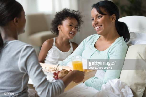 Sisters bring mother breakfast in bed