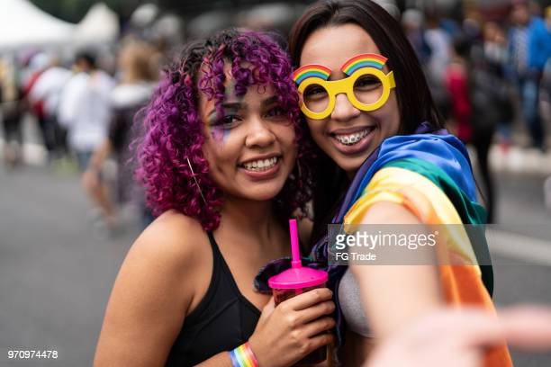 sisters celebrating carnival at street - lgbtqi pride event stock pictures, royalty-free photos & images