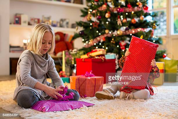 Sisters checking presents by Christmas tree