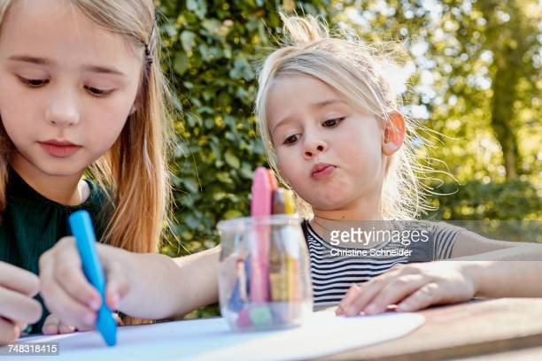 Sisters colouring out in garden