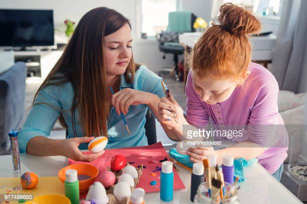 """sisters crafting easter decorations at home. - """"martine doucet"""" or martinedoucet stock pictures, royalty-free photos & images"""