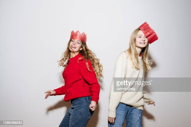 sisters dancing in christmas hats to celebrate holidays - crown stock pictures, royalty-free photos & images