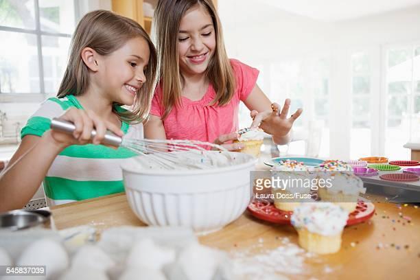 Sisters decorating cupcakes