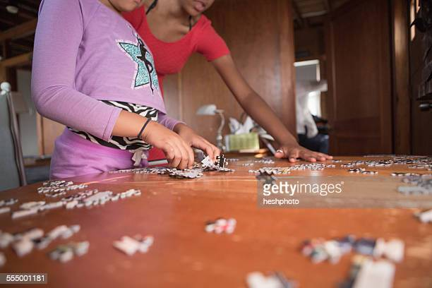 sisters doing a puzzle on summer vacation - heshphoto imagens e fotografias de stock