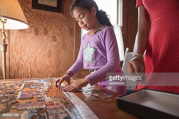 sisters doing a puzzle on summer vacation - heshphoto stock pictures, royalty-free photos & images