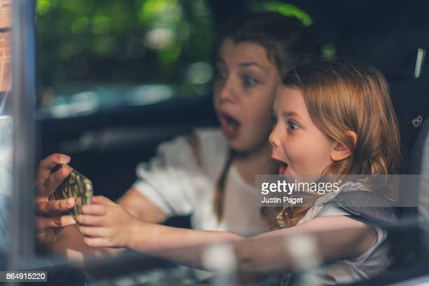 Sisters doing silly face selfie in car