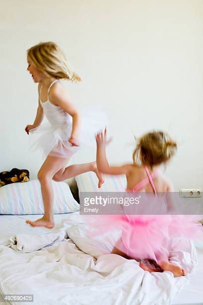 Sisters dressed as ballet dancers running on bed