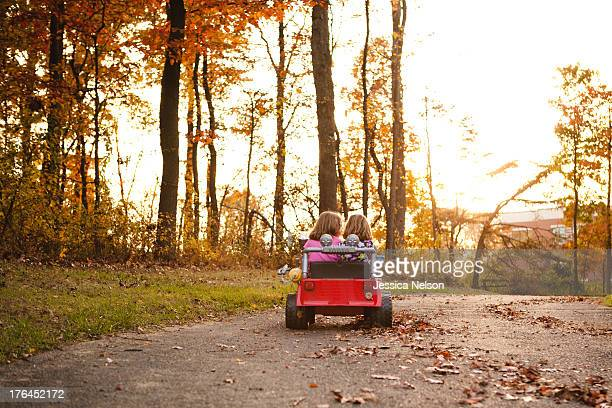 Sisters Driving in Toy Car