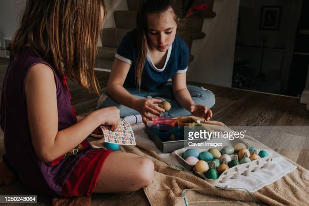 sisters dying chicken eggs inside the house - dirty easter stock pictures, royalty-free photos & images