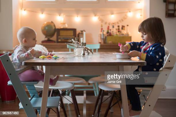 Sisters (12-17 months, 2-3) eating at table