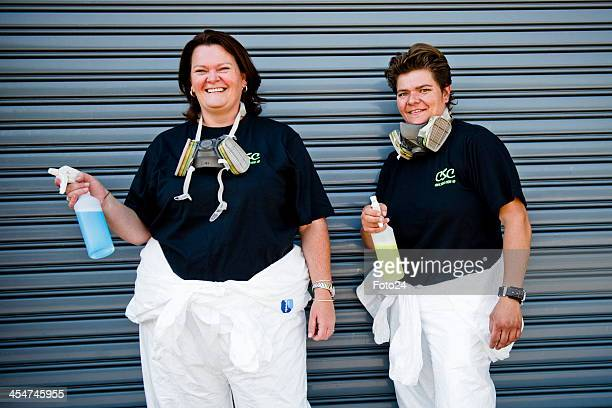 Sisters Eileen de Jager and Roelien Schutte who make a living from cleaning up crime scenes pose together in their cleaning kit on November 30 2012...