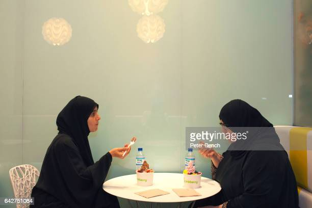 Sisters enjoy a Pinkberry together in the Mall of the Emirates a premier shopping mall in the Al Barsha district of Dubai UAE