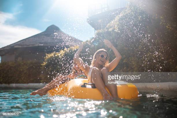 sisters enjoying on inflatable ring at park - fun stock pictures, royalty-free photos & images